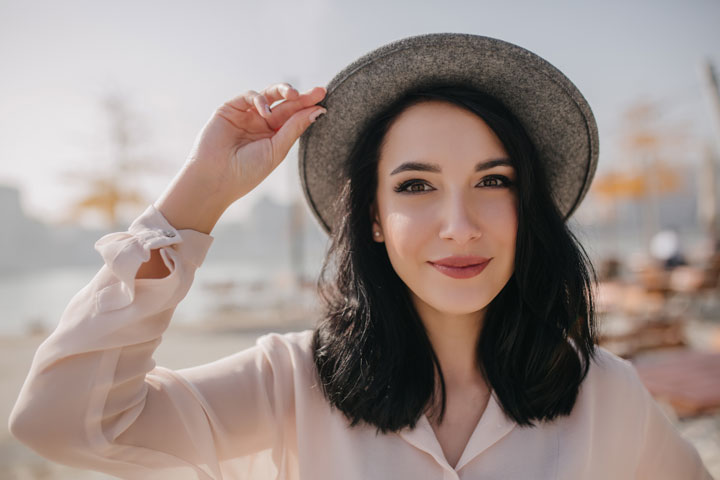 positive brunette woman in hat
